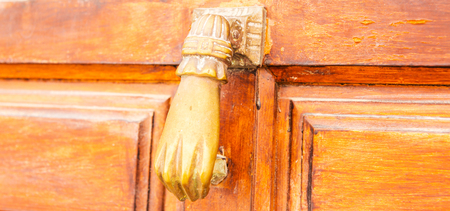 Door with brass knocker in the shape of a hand,  beautiful entrance to the house, vintage decoration Stock Photo