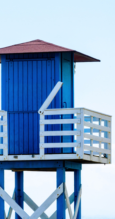 Blue rescue hut on a sandy beach, safe relax by the ocean, a beautiful sunny day, vacation