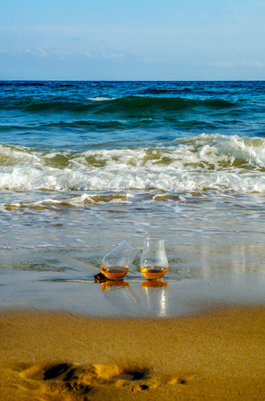 Glass of whiskey single malt on the sand washed by the waves, a glass of tasting, relax on the beach, vacation Standard-Bild