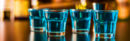 Popular blue drink shot kamikaze on the background of the bar with bottles, a refreshing drink, party night