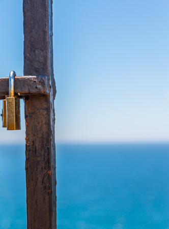 Rusty padlock attached to a balustrade by the sea, a traditional way of showing love, relationship Stock Photo