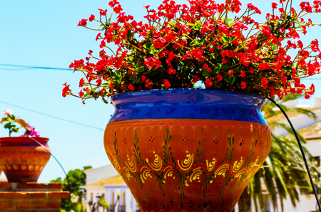 Beautiful ceramic flower pot on a pedestal with flowers, decoration of urban space, outdoor decoration, decor street