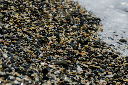 Pebble beach washed by sea waves, small and various stones forming the shore, nature