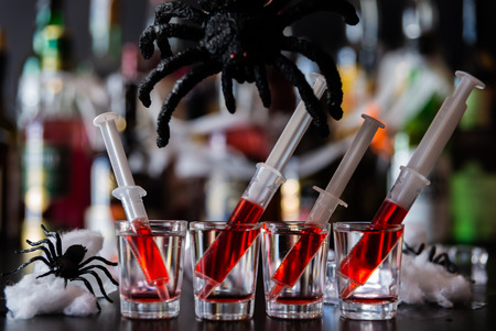 Creepy Halloween party cocktails with syringes of grenadine syrup as blood, shot drinks at party, scary bar