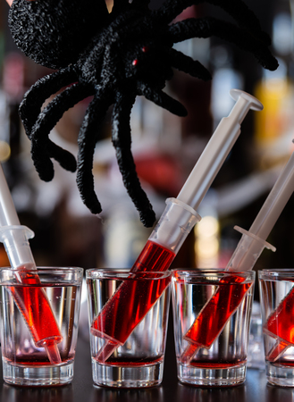 Creepy Halloween party cocktails with spider and syringes of grenadine syrup as blood, shot drinks at party, scary bar Stock Photo