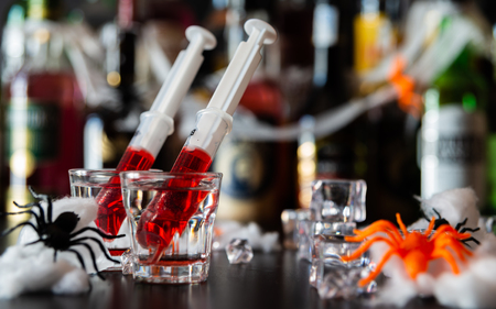 Creepy Halloween party cocktails with spiders and syringes of grenadine syrup as blood, shot drinks at party, scary bar