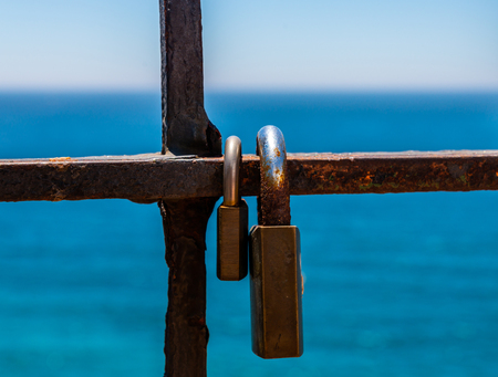 Rusty padlock attached to a balustrade by the sea, a traditional way of showing love, relationship Archivio Fotografico