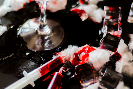 Creepy Halloween party cocktails with syringes of grenadine syrup as blood and ice cubes, shot drinks at party, scary bar Stock Photo