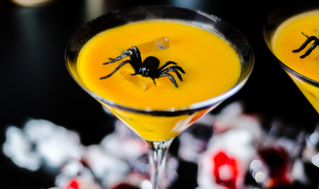 Creepy Halloween party cocktails with blood, spiders and ice cubes, drinks at party