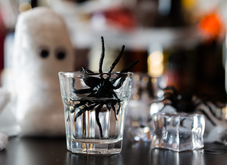Creepy Halloween party cocktails with spiders and ice cubes, drinks at party Stock Photo
