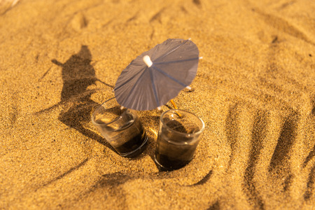 Two glasses of water on a sandy beach with umbrellas for drinks, summer relax
