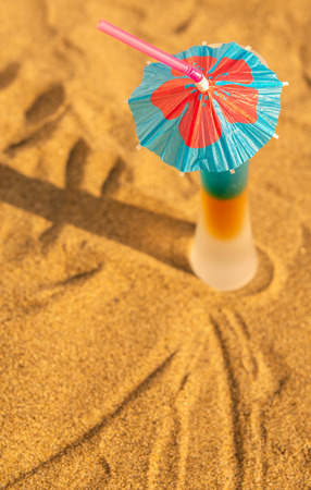Colorful shots drinks on a sandy beach with umbrellas for drinks, summer relax