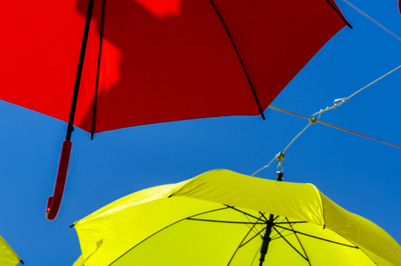 Colorful umbrellas urban street decoration. Hanging colorful umbrellas over blue sky, tourist attraction, sunny day Stock Photo