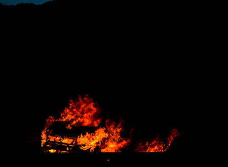 Burning car on the road at night, a tragic accident ending with the ignition of a car, tragedy Stock Photo