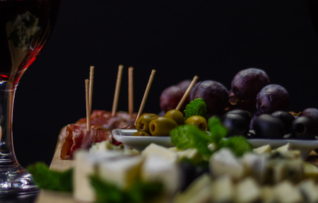 Red wine and set of different cheeses on a wooden board, delicious snack, healthy and exclusive food
