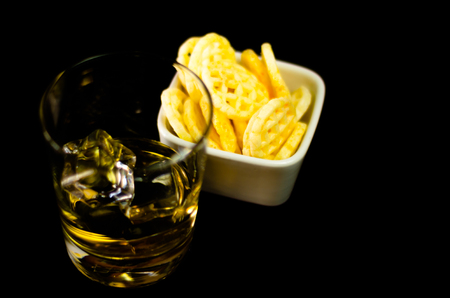 Glass of whiskey with ice cubes and salty snacks on the background of the bar, party time