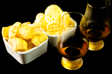 Glasses of whiskey with salty snacks on the background of the bar, party time 版權商用圖片