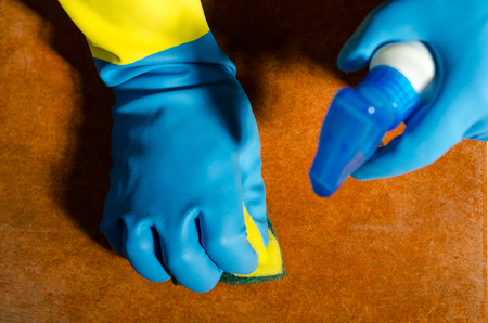 Hands in rubber gloves cleaning the surfaces of ceramic tiles, safe and hygienic cleaning, keeping the house clean