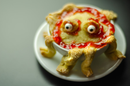 Cake baked in the shape of a monster in a ceramic bowl, sweet for Halloween, scary food Stock Photo
