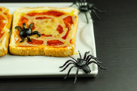 Funny sandwiches with  spider and  spider web for Halloween party, scary food Фото со стока
