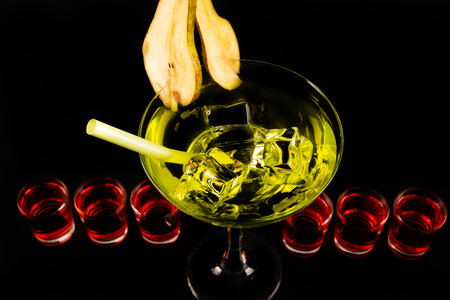 Green refreshing drink on the basis of pear on a black background, party night Фото со стока