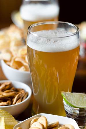 Pint of lager beer in a glass, set of various snacks, a standard set of drinking and eating in a pub, beer and snacks
