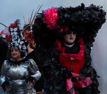 NERJA, SPAIN - FEBRUARY 11, 2018 People in costumes celebrating Burial of the Sardine in   Malaga province, funeral parade, carnival