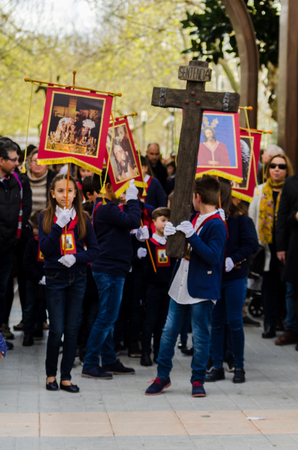 Procession of children starting the holy week. Children in the procession wear platforms with images of saints. Traditional celebration of the Catholic holiday in Andalusia.