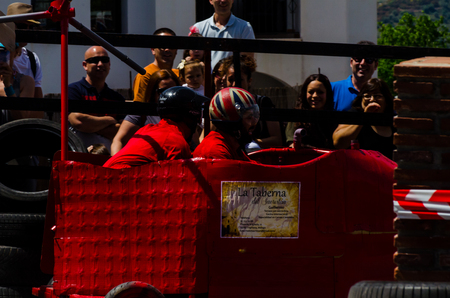 FRIGILIANA, SPAIN - MAY 13, 2018 Autos Locos - traditional fun involving the ride of cardboard cars in small spanish town, self-made vehicles, creative and cheerful event Editorial
