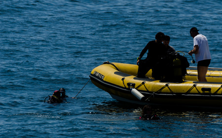 LA HERRADURA, SPAIN - JUNE 14, 2018 People on a pontoon preparing to dive and discover the underwater world, active sport