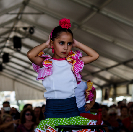 TORRE DEL MAR, SPAIN - JULY 22, 2018 show of Latin dance performed by a dance group in the rhythm of Spanish music, children in folk costumes performing in front of the audience, dance show