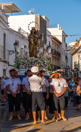 NERJA, SPAIN - JULY 16, 2018 people participating in the celebration of the Catholic ceremony of transferring the holy figure in Spain. The Virgen del Carmen is the patron saint and protector of fishermen and sailors 新聞圖片