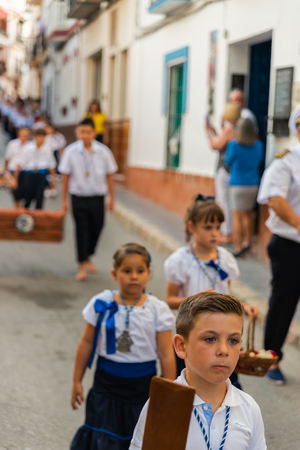 NERJA, SPAIN - JULY 16, 2018 people participating in the celebration of the Catholic ceremony of transferring the holy figure in Spain. The 'Virgen del Carmen' is the patron saint and protector of fishermen and sailors