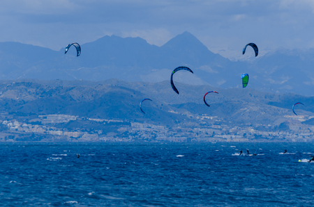 MALAGA, SPAIN - MAY 25, 2018 People practicing active sport, wave riding using power kite in a windy bay