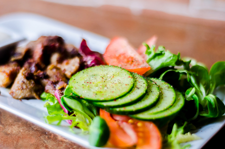 Tasty dish with pork, lettuce, tomato and cucumber on a white plate with a dip, healthy meal 스톡 콘텐츠 - 114953280
