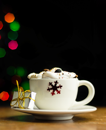 Christmas coffee with whipped cream and a small gift on the background bokeh lights, xmas