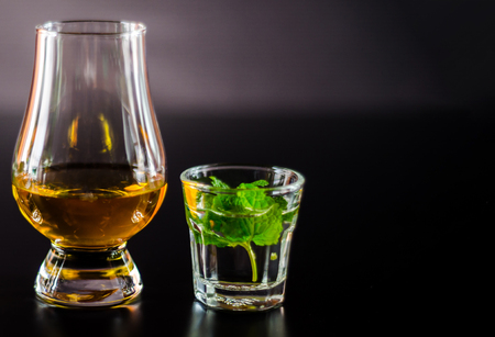 Single malt whiskey in a glass and green mint liqueur, refreshing set of drinks, taste sensations