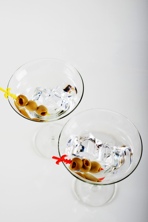 Gin with vermouth in a glass on a white background, classic cocktail served with olives, party night