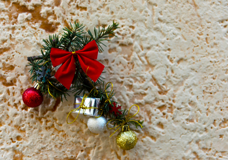 Green Christmas ornament with ball, bow and small gifts  on a wall background, xmas decoration Stock Photo