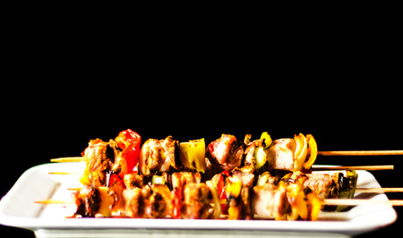 Grilled skewers of meat and vegetables on a wooden board, colorful and tasty dish, tasty meal 版權商用圖片