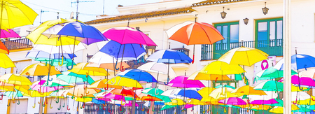 Colourful umbrellas urban street decoration. Hanging colorful umbrellas over blue sky,watercolor