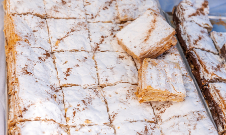Set of portions of creamy layer cake napoleon on a baking sheet, delicious sweetness 写真素材