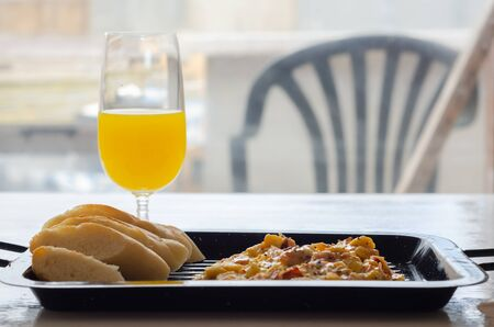 Scrambled eggs served with orange juice and fresh baguette, morning food