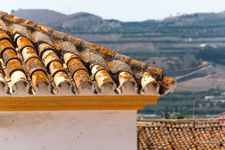 Traditional old Spanish ceramic roof tiles on a building, characteristic elements of Mediterranean architecture, vintage