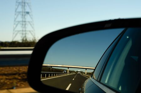 view in the car mirror on fast road in the Spain, beautiful landscape, transportation Banco de Imagens