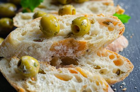 Baguette stuffed with olives, cut with fresh green olives and parsley, served on a stone plate, healthy appetizer