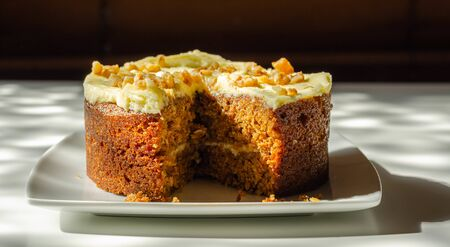 Carrot cake filled and topped with cream cheese buttercream and decorated with walnuts, bakery