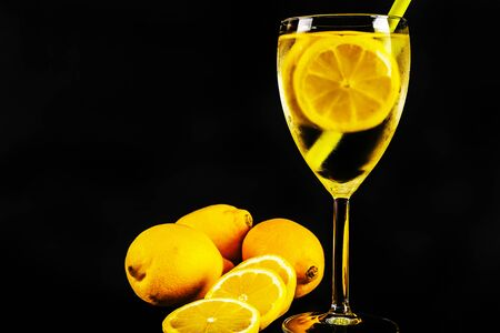 Lemon slices in a transparent drink in a glass on a black background, tropical fruits