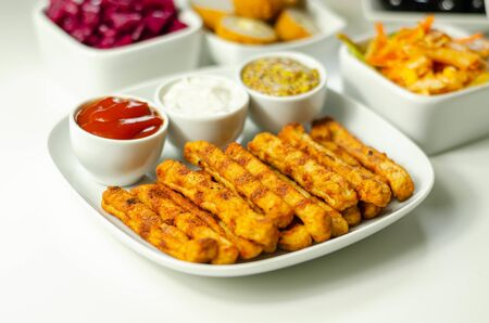 Roast chicken formed in straws, bites of succulent chicken breast with different sauces, party food