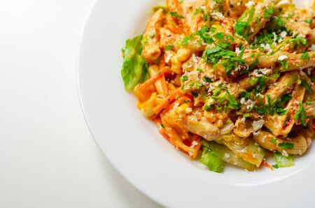 Piri piri style chicken on a bed of wholewheat pasta and vegetables, with a cool sour cream and chive dressing, healthy lifestyle